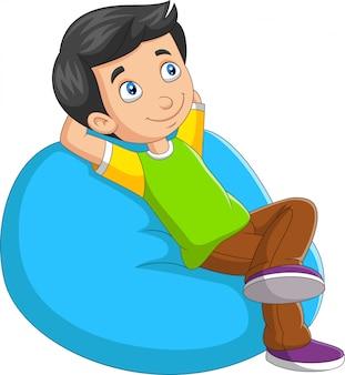 Kleiner junge der karikatur, der auf sofa sich entspannt