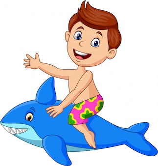 Kleiner junge der karikatur, der einen aufblasbaren haifisch reitet
