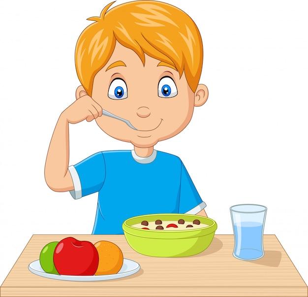 Kleiner junge der karikatur, der frühstückskost aus getreide mit früchten isst