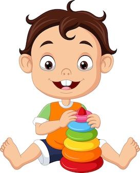 Kleiner junge der karikatur, der mit buntem pyramidenspielzeug spielt