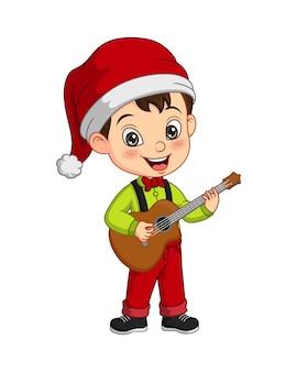Kleiner junge der karikatur, der weihnachtskostüm trägt, der gitarre spielt