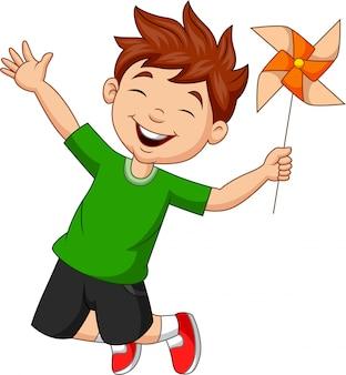 Kleiner junge, der mit einer papierwindmühle springt