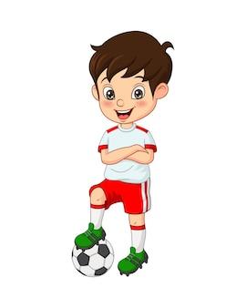 Kleiner junge gekleidet in einer fußballuniform mit fußball