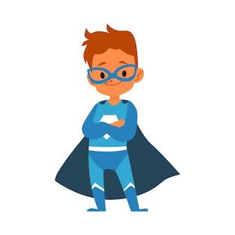 Kleiner junge im blauen superheldenkostüm, das karikaturart der gefalteten arme steht, lokalisiert auf weißem hintergrund. junge kind gekleidet in umhang und maske in tapferer heldenhaltung mit verschränkten armen
