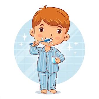 Kleiner junge im pyjama steht beim zähneputzen und hält ein glas wasser im badezimmer