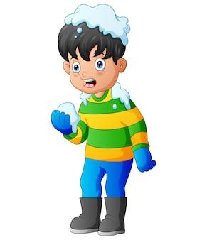 Kleiner junge in der winterkleidung, die einen schneeball spielt
