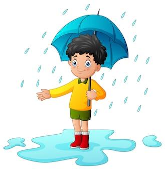 Kleiner junge mit regenschirm unter dem regen