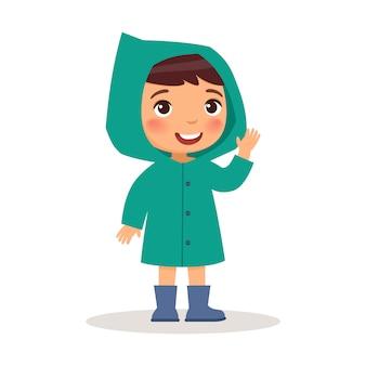 Kleiner junge steht in einem türkisfarbenen regenmantel und blauen gummistiefeln.