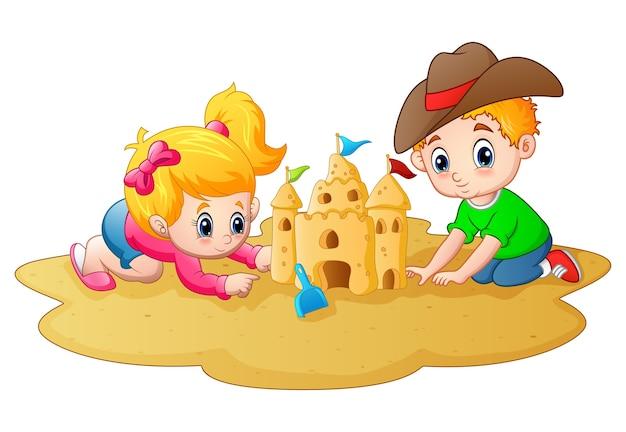 Kleiner junge und mädchen, die sandburg am strand bildet