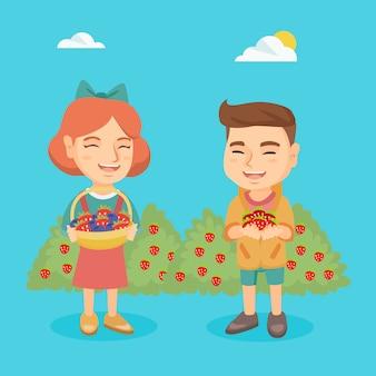 Kleiner junge und mädchen mit erdbeere und blaubeere.