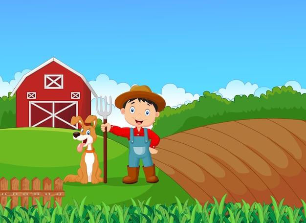 Kleiner landwirt der karikatur und sein hund mit bauernhofhintergrund
