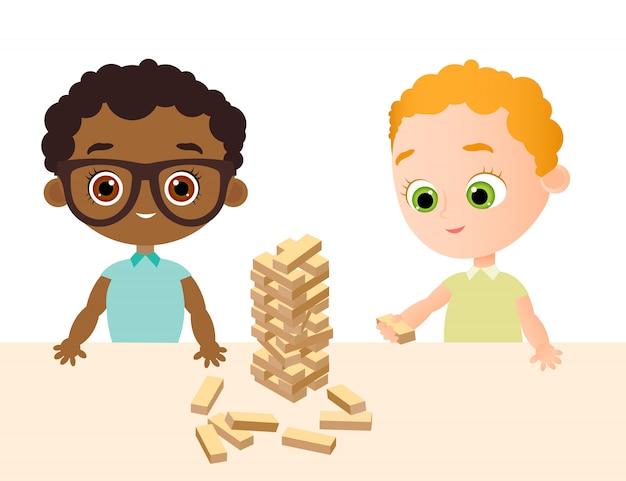Kleines babyspiel im hölzernen spiel. african american boy mit brille. turm aus holzwürfeln.