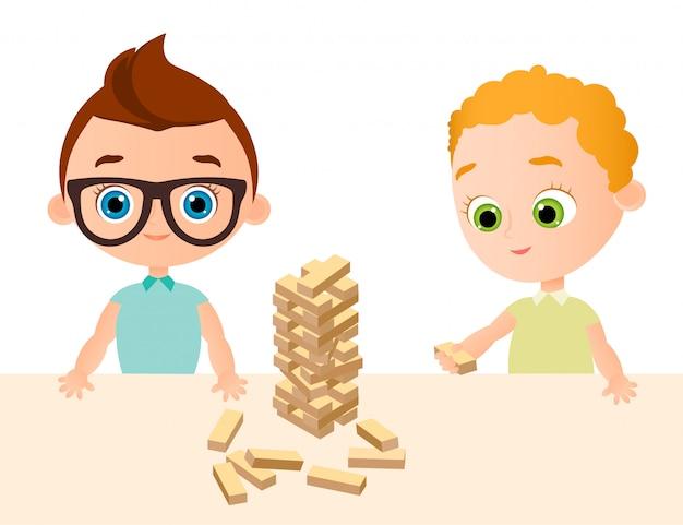 Kleines babyspiel im hölzernen spiel. junge mit brille. turm aus holzwürfeln.