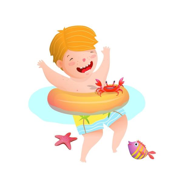 Kleines jungenkind, das mit seekrabbenfisch und stern im ozean schwimmt, der mit aufblasbarem ring schwimmt.