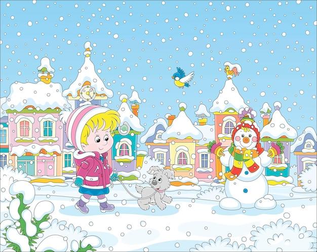 Kleines kind, das mit einem fröhlichen welpen durch einen schneebedeckten park spaziert