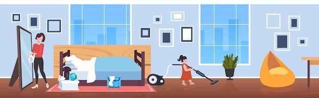 Kleines kind mit staubsauger mutter sprühen und wischen spiegel familie tun hausarbeit reinigung service-konzept moderne wohnzimmer innen horizontale in voller länge skizze