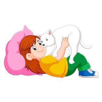 Kleines mädchen, das auf dem bett mit ihrem kätzchen sich entspannt
