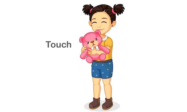 Kleines mädchen, das einen teddy hält, der einen berührungssinn zeigt