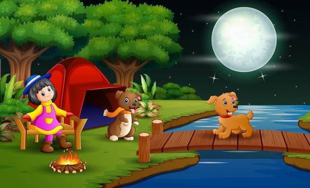 Kleines mädchen, das im wald nachts mit ihrem haustier kampiert