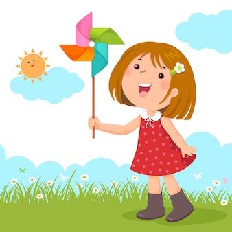 Kleines mädchen, das mit einem bunten windmühlenspielzeug spielt
