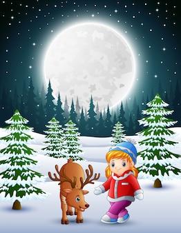 Kleines mädchen, das nachts mit einem hirsch im schneebedeckten garten spielt