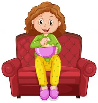 Kleines mädchen, das snack auf dem stuhl isst