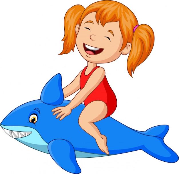 Kleines mädchen der karikatur, das aufblasbaren haifisch reitet