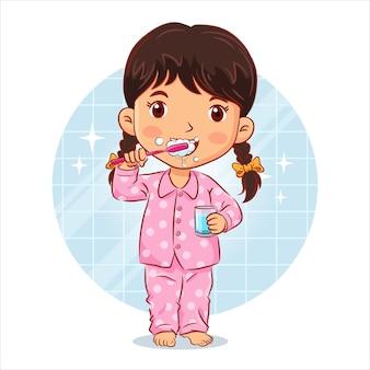 Kleines mädchen im pyjama steht beim zähneputzen und hält ein glas wasser im badezimmer
