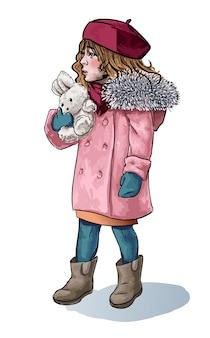 Kleines mädchen im wintertuch mit der gezeichneten handgezeichneten skizze des flauschigen spielzeugs des hasenkaninchens.