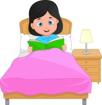 Kleines mädchen liest ein buch vor dem schlafengehen