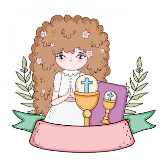 Kleines mädchen mit bibel in der ersten kommunionfeier