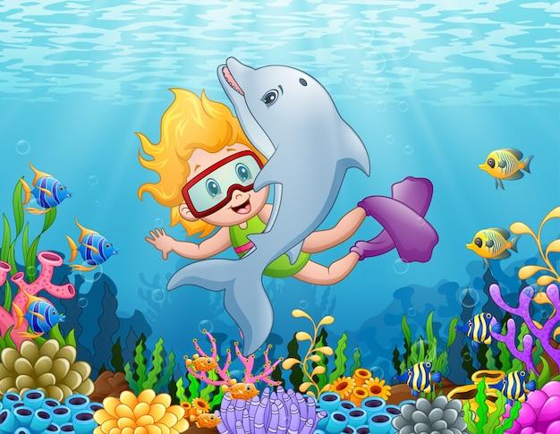 Kleines mädchen mit delphinschwimmen unter dem meer
