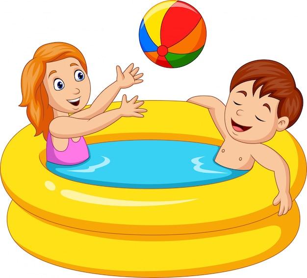 Kleines mädchen und junge, die in einem aufblasbaren pool spielen