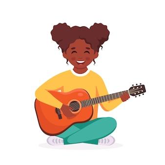 Kleines schwarzes mädchen spielt gitarre kind spielt musikinstrument