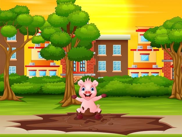 Kleines schwein, das eine schlammpfütze im stadtpark spielt