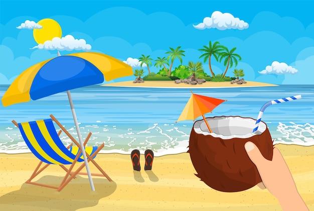 Kokosnuss mit kaltem getränk in der hand. landschaft mit hölzerner chaiselongue, regenschirm, flip-flops am strand. tag im tropischen ort.