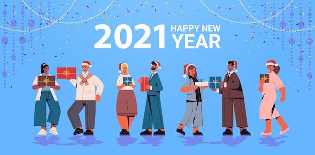 Kollegen in santa hüte halten geschenke mischen rennen büroangestellte feiern 2021 neujahr und weihnachtsferien grußkarte horizontale vektor-illustration in voller länge