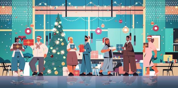 Kollegen in weihnachtsmützen, die geschenke halten, mischen rassenmitarbeiter, die neujahrs- und weihnachtsferienbüroinnenraum horizontale vektorillustration in voller länge feiern