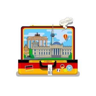 Konzept der reise nach deutschland oder deutsch lernen. deutsche flagge mit wahrzeichen im offenen koffer