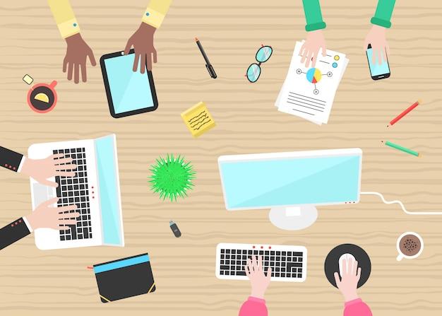 Konzept der teamarbeit mit den händen und den gegenständen auf holztisch