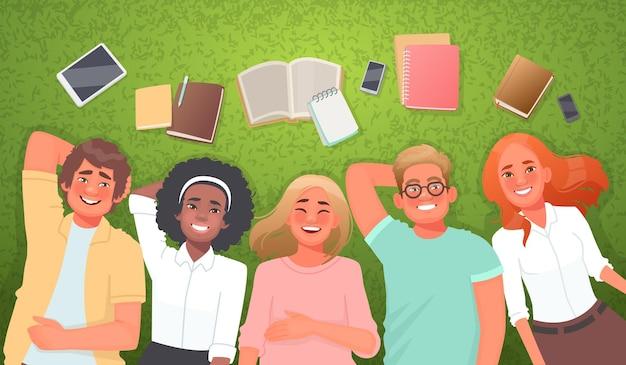 Konzept des studentenlebens und der freundschaft glückliche freunde jungen mädchen auf dem rasen mit büchern und geräten