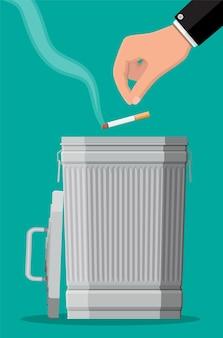 Konzept des tabakmissbrauchs. hand, die zigaretten in den papierkorb legt. rauchen verboten. ablehnung, vorschlag rauch.