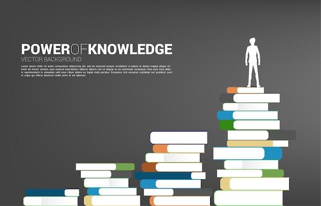 Konzept hintergrund für die kraft des wissens. schattenbild des geschäftsmannes, der auf stapel von büchern steht.