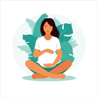 Konzept schwangerschaft, mutterschaft. schwangere frau mit natur verlässt hintergrund.