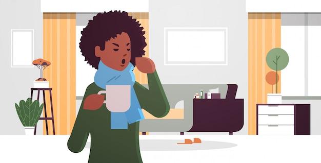 Kranke frau, die niesen trinkt heißen tee ungesundes afroamerikanisches mädchen im schal, das an kaltem grippevirus-krankheitskonzept leidet modernes wohnzimmerinnenraum-flachporträt horizontal