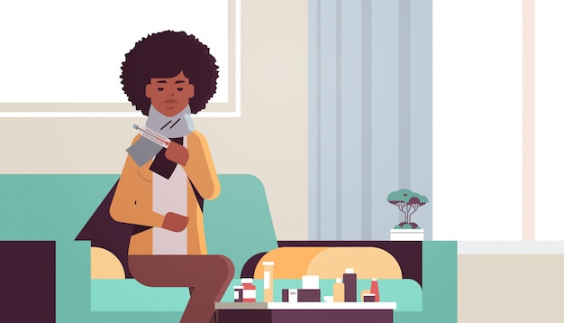 Kranke frau, die temperatur mit thermometer ungesundes afroamerikanisches mädchen im schal leidet, das an kaltem grippevirus-krankheitskonzept leidet modernes wohnzimmerinnenwohnungsporträt horizontal
