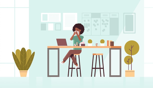 Kranke geschäftsfrau, die nase mit taschentuch afroamerikanermädchen sitzend am arbeitsplatz unter verwendung der laptop-frau mit grippe niest krankheitskonzept modernes büro interieur in voller länge horizontal bläst