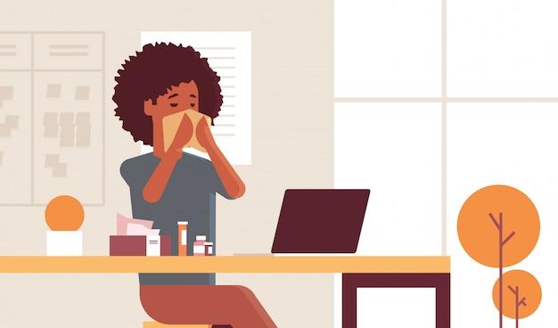 Kranke geschäftsfrau, die nase mit taschentuch-afroamerikanermädchen sitzt, das am arbeitsplatz unter verwendung der laptopfrau sitzt, die grippe-nieskrankheitskonzept modernes büroinnenporträt horizontal trägt
