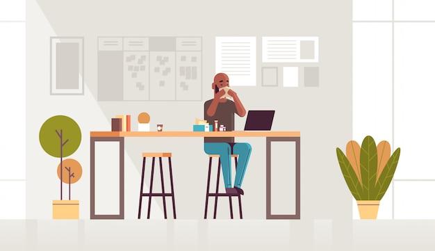 Kranker geschäftsmann, der nase mit taschentuch afroamerikaner kerl sitzt am arbeitsplatz unter verwendung von laptop-mann mit grippe niesen krankheit konzept modernes büro interieur in voller länge horizontal