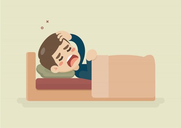 Kranker junger mann, der unter kopfschmerzen liegt im bett leidet